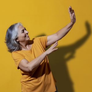 Portrait of a happy grandmother dancing. (Senior)